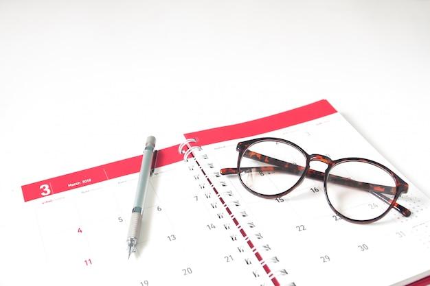 März-kalendertagebuch mit eyewear und stift auf weißem hintergrund