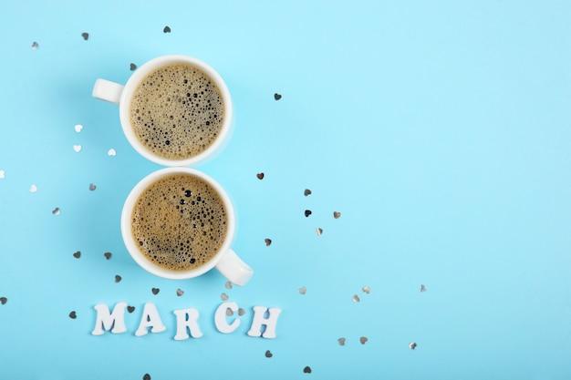 März text mit tassen kaffee und glitzer auf blauem hintergrund