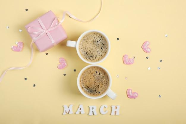März text mit tassen kaffee und rosa geschenk und herzen auf gelbem hintergrund