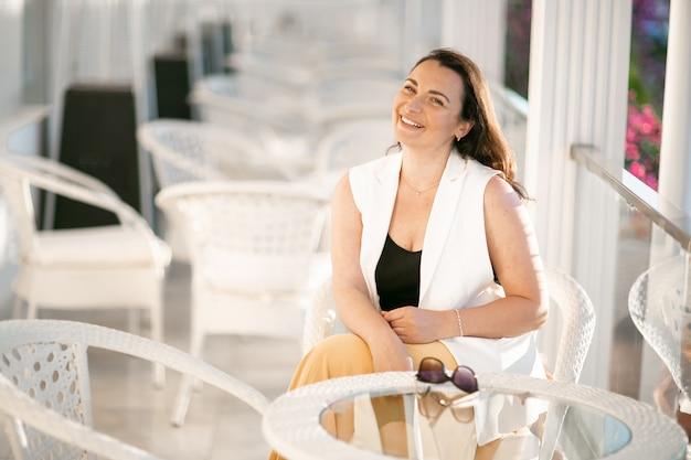 Mäßig fettleibige geschäftsfrau, die in einem café sitzt, während kaffee hält