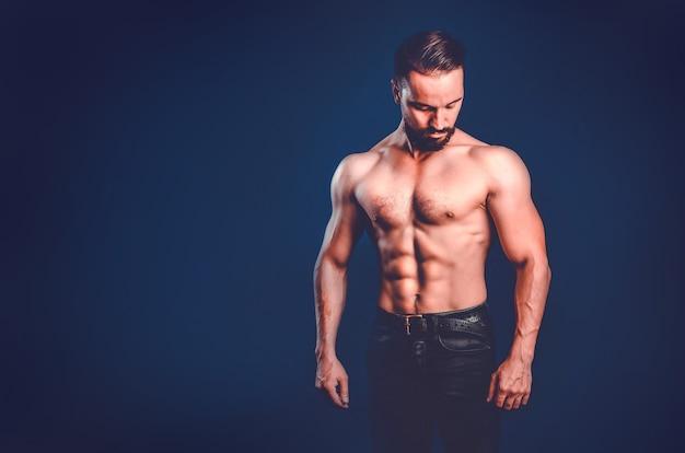 Mäßig gepumptes männliches fitnessmodell mit geprägten muskeln, kopierraum