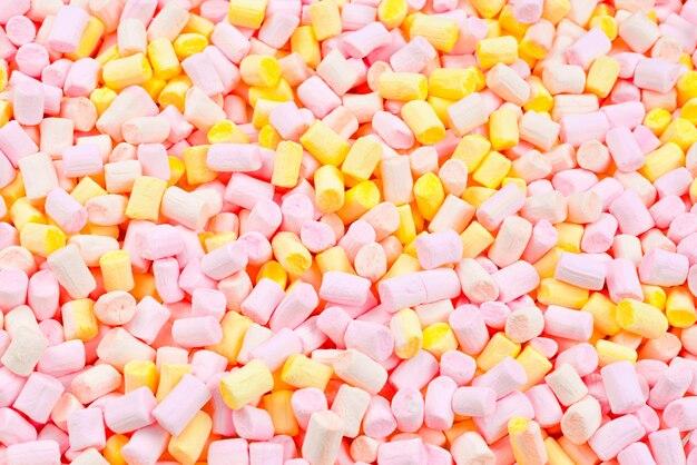 Mäusespeck. hintergrund der rosa und gelben bunten mini-marshmallows.
