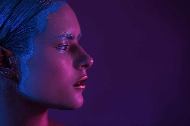Magenta halbes gesicht des schönen jungen mädchens high fashion model im neonlicht