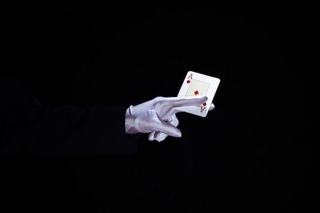Magier, der spielkarte der asse in den fingern gegen schwarzen hintergrund hält