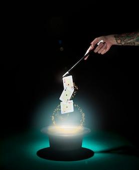 Magier, der spielkartentrick über dem zylinder mit glühenden lichtern gegen schwarzen hintergrund durchführt