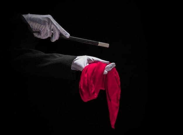 Magier, der trick auf roter serviette mit magischem stab gegen schwarzen hintergrund durchführt