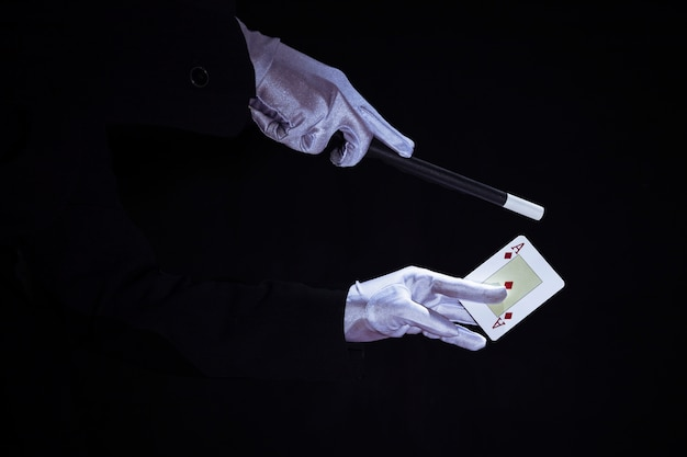 Magier, der trick auf spielkarte der asse gegen schwarzen hintergrund durchführt