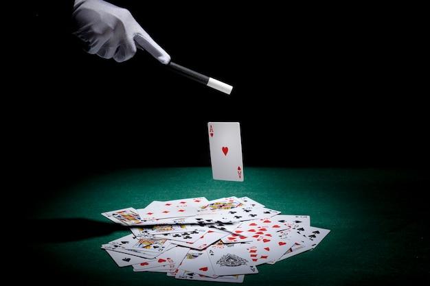 Magier, der trick auf spielkarten mit magischem stab auf schürhakentabelle durchführt