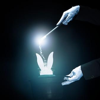 Magier, der trick mit magischem stab gegen schwarzen glühenden hintergrund durchführt