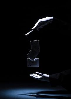 Magier, der trick mit magischem stab gegen schwarzen hintergrund durchführt