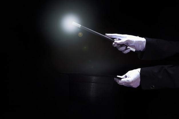 Magier, der trick mit magischem stab über dem schwarzen zylinder gegen schwarzen hintergrund durchführt