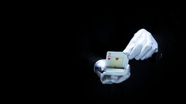 Magier, der trick mit spielkarten gegen schwarzen hintergrund durchführt