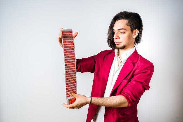 Magier mischt ein kartenspiel, geschick und geschicklichkeit, um seine kunden zu täuschen.