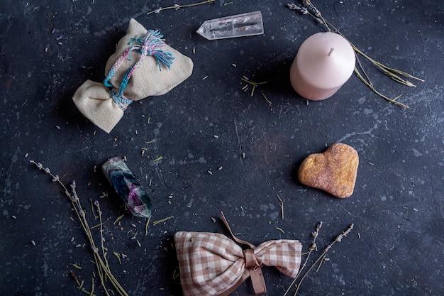 Magische flache lay-komposition mit rosa kerze, kristallen, heidnischer tasche und blumen