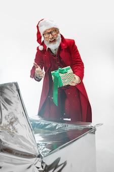 Magische geschenkbox. moderner stilvoller weihnachtsmann im roten modischen anzug lokalisiert auf weißem hintergrund. sieht aus wie ein rockstar. silvester und heiligabend, feiern, feiertage, winterstimmung, mode.