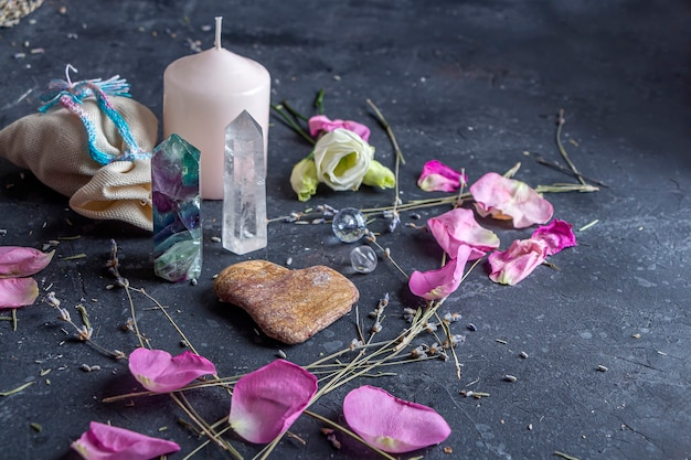 Magische komposition mit rosa kerze, kristallen, heidnischem beutel und blumen.