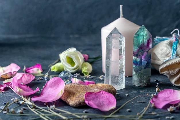 Magische komposition mit rosa kerze, kristallen, heidnischer tasche und blumen.
