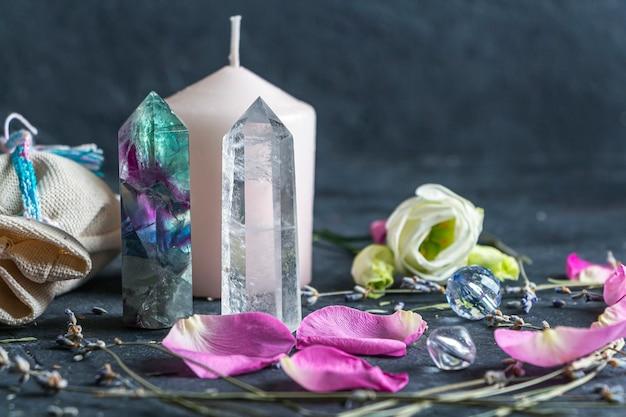 Magische komposition mit rosa kerze, kristallen, heidnischer tasche und blumen