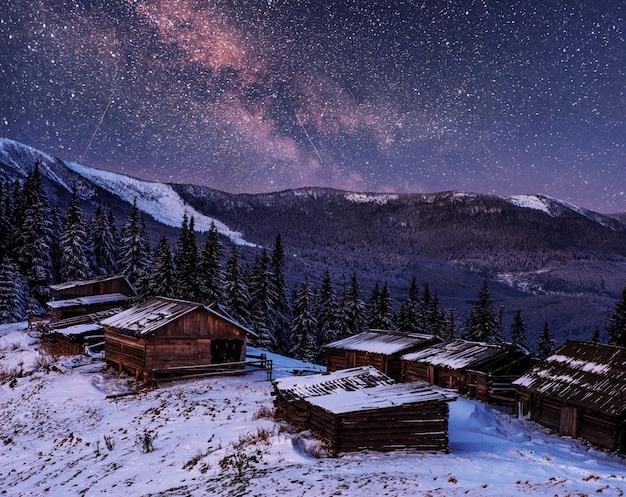 Magische schneebedeckte winterbäume und bergdorf. lebendiger nachthimmel mit sternen und nebel und galaxie.