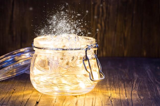 Magische weihnachtsgirlande mit hellen lichtern innerhalb eines glasgefäßes