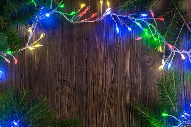 Magische weihnachtsgirlande mit hellen lichtern und tannenbaumasten auf holz