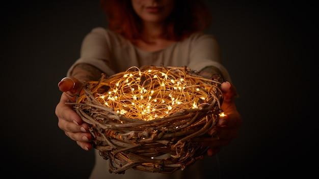 Magische weihnachtskarte mit schönen funkelnden weihnachtslichtern mit nest in den händen