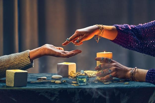 Magische zigeunerfrau, die palmenlinien um kerzen und andere magische accessoires liest. hexe während der wahrsagerei, vorhersage des zukünftigen lebens und wahrsagungsrituals