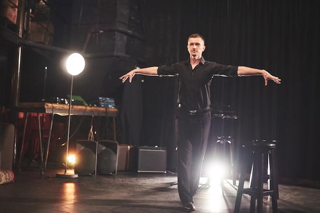Magischer blick. hübscher junger mann in der schwarzen kleidung beim sitzen auf stuhl nahe im dunklen raum mit licht.