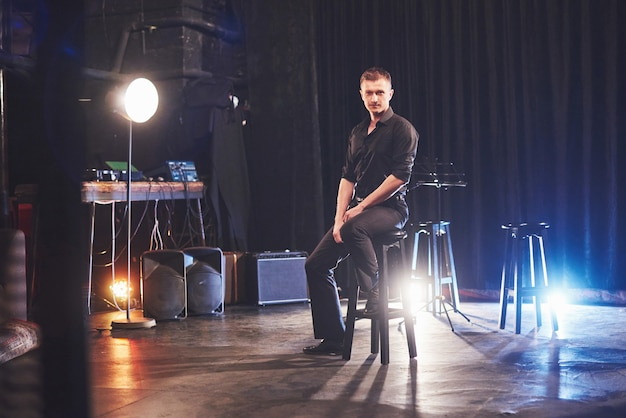 Magischer blick. hübscher junger mann in der schwarzen kleidung, die auf stuhl nahe im dunklen raum mit licht sitzt.