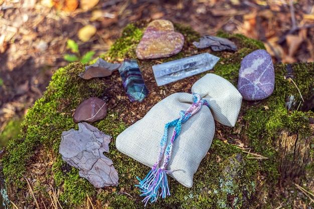 Magischer fluorit, quarzkristall, kerze und beutel mit trank. felsen für mystisches ritual, hexerei