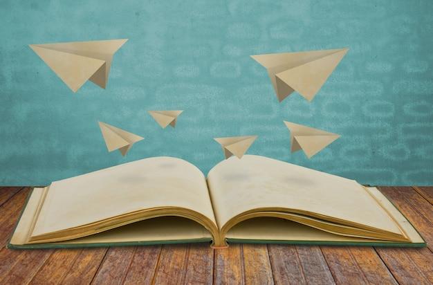 Magisches buch mit papierflugzeug