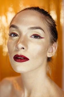 Magisches mädchen-porträt in gold. goldenes make-up, nahaufnahmeporträt in studioaufnahme, farbe. beauty model girl mit perfektem hellem make-up, roten lippen, goldenem kastanienbraunem schmuck. sexy lady make-up urlaubsparty.