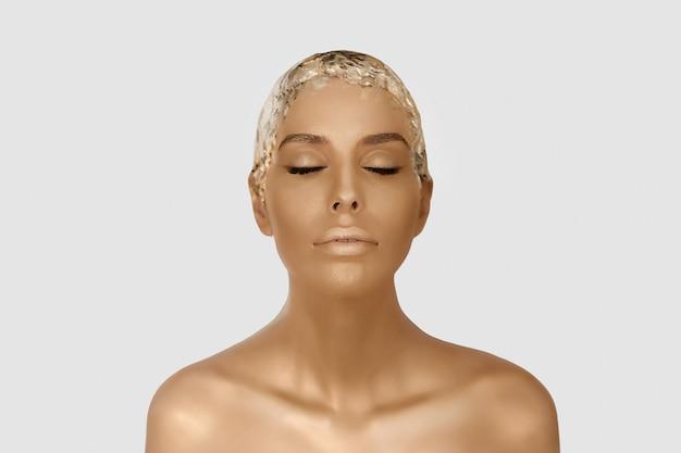 Magisches mädchenportrait mit goldhaut. goldenes kreatives make-up, nahaufnahmeporträt in studio sh