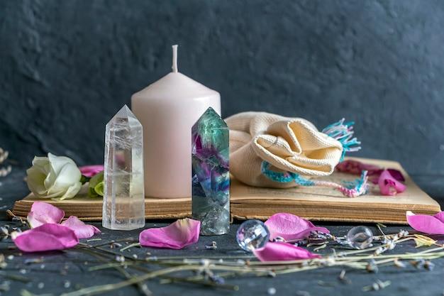 Magisches stillleben mit rosa kerze, altem buch, kristallen und heidnischer tasche
