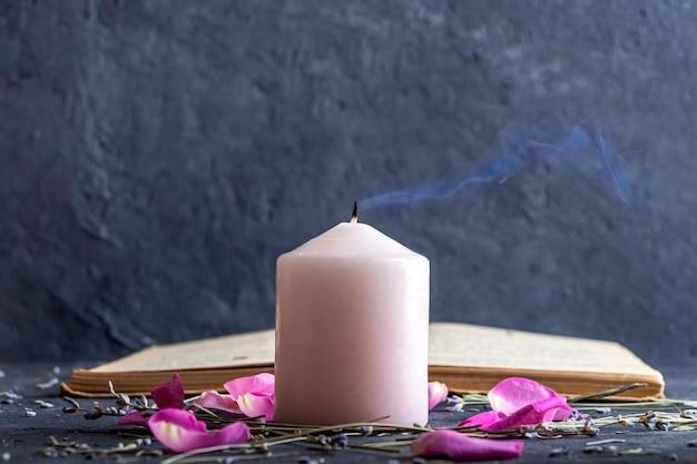 Magisches stillleben mit rosa kerze und altem kräuterbuch