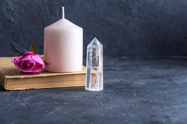 Magisches vintage-stillleben mit kristallen, rosa kerze, altem buch und rosenblumen.