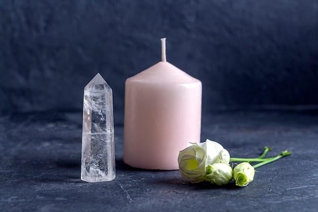 Magisches vintage-stillleben mit kristallen, rosa kerze und rosenblüten.