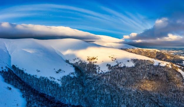 Magisches winterpanorama von schönen schneebedeckten pisten in einem skigebiet in europa an einem sonnigen, windstillen, frostigen tag. das konzept der aktiven erholung im winter