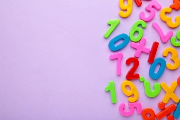 Magnetische mehrfarbige figuren auf violettem hintergrund mit kopienraum. zurück zur schule.