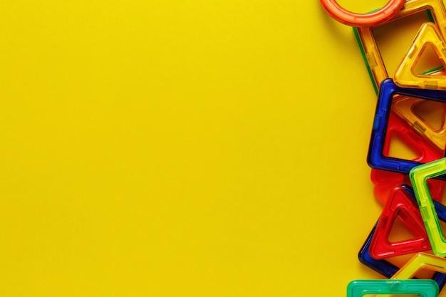Magnetischer designer oder konstrukteur für kinder. details, geometrische formen auf gelbem hintergrund. flache lage, kopierraum.