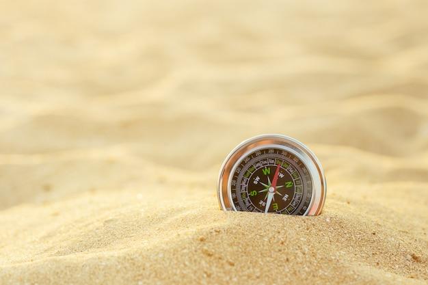 Magnetischer silberner kompaß auf sand