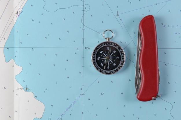 Magnetkompass und klappmesser auf einem nautischen navigationsma