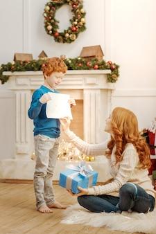 Magst du es, mama? fröhliches kind lächelt, während es seiner mutter eine neue zeichnung zeigt, während beide zeit zusammen an einem weihnachtsmorgen verbringen.