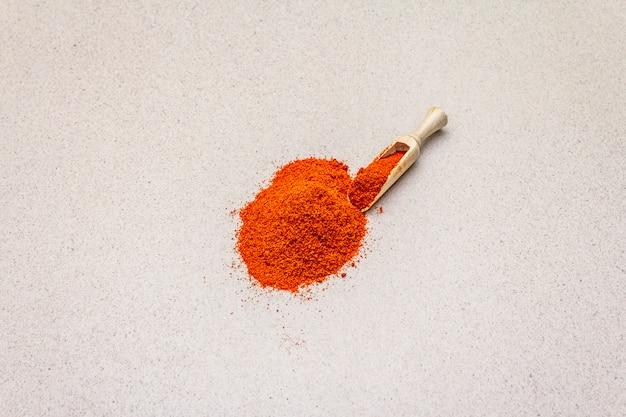 Magyar leuchtend rotes süßes paprikapulver. traditionelle zutat zum kochen gesundes essen. holzschaufel, steinbeton