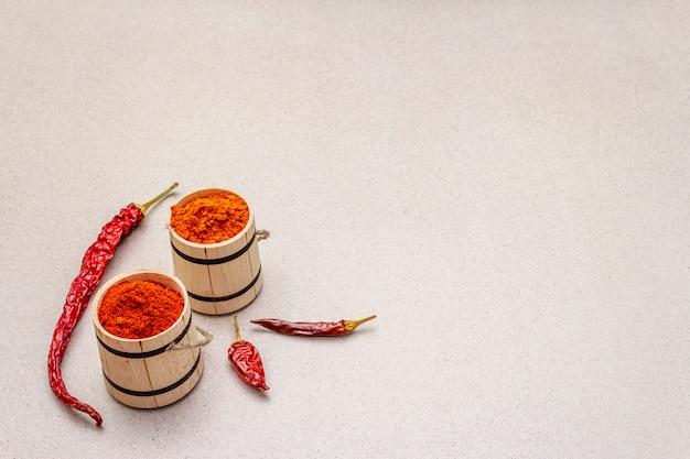 Magyar (ungarisches) rotes süßes und heißes paprikapulver. traditionelles gewürz zum kochen von nationalgerichten, verschiedene sorten von trockenem pfeffer. holzfässer,