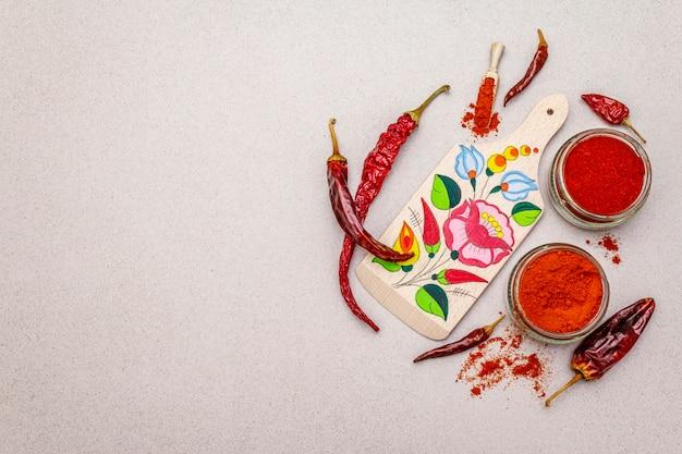 Magyar (ungarisches) rotes süßes und heißes paprikapulver. traditionelles muster auf einem schneidebrett, verschiedene sorten trockener pfeffer.