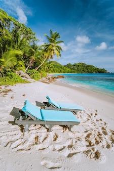 Mahe, seychellen. zwei sonnenliegen am schönen anse intendance beach. blauer ozean, weißer sand und kokospalmen. reiseerholungskonzept.