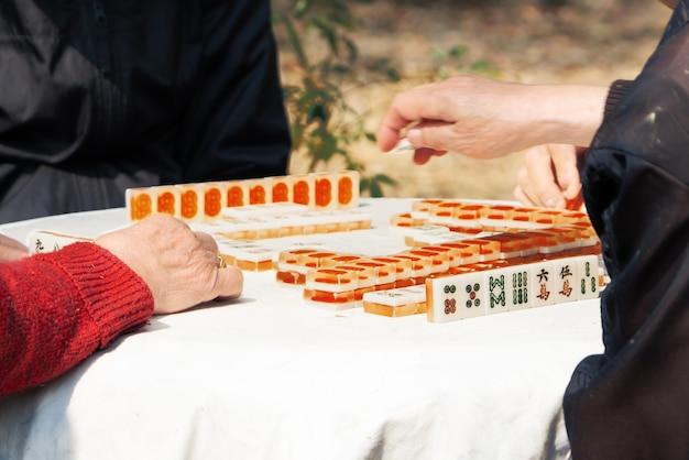 Mahjong-tischspiel des chinesischen seniors auf stadtstraße