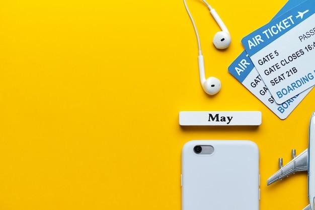 Mai urlaubskonzept neben tickets und flugzeugmodell auf gelbem hintergrund mit kopienraum.