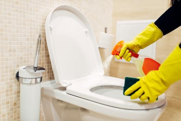 Maid reinigt das bidet mit einem reinigungsspray